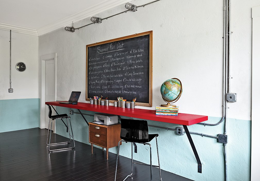 """The tables in the kids' study hall are """"plywood specials,"""" David's term for the furniture he built himself.  """"There is something so good about living in the South: the culture, the innovation, the values, the thrift,"""" he says.  Photo 2 of 13 in Family-Friendly Renovation of a Brick Warehouse in Alabama"""