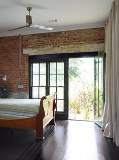 Throughout the house, as in the master bedroom, industrial ceiling fans from Westinghouse, combined with the thick brick walls, keep the need for air conditioning to a minimum. The bed is from Bob Timberlake.