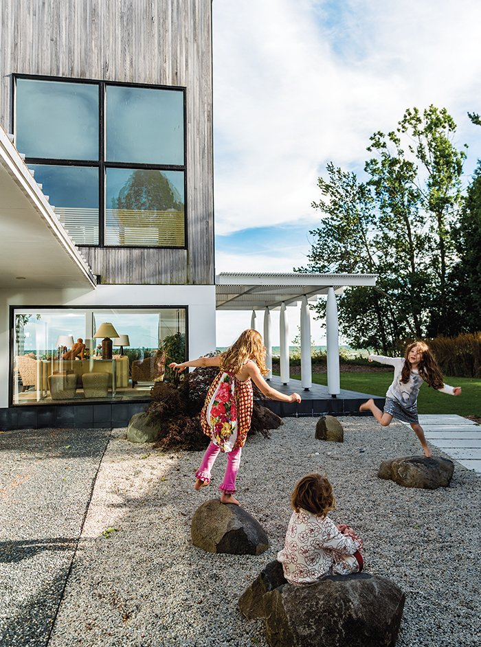 """Exterior and Wood Siding Material Julie Brogan's three grandchildren—frequent visitors to her lakeside house in Sturgeon Bay, Wisconsin—can often be found playing on the crushed slate in the courtyard or romping in a corridor that has come to be known as the """"galloping hall.""""  Photo 1 of 8 in A Modern Lakeside Home in Wisconsin"""
