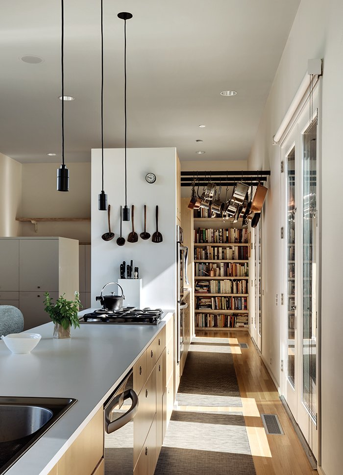 Orrill, a culinary professional, used Ikea's kitchen planning software to plot out cabinetry and appliance placement. Levy split the 30-foot-long space into a private back kitchen, with an oven and staging area, and a public cooking station with a white laminate countertop—a maneuver that means guests in the adjacent dining area never see the messy stuff.  Photo 4 of 9 in A Light-Filled, Nature-Inspired House in Dallas