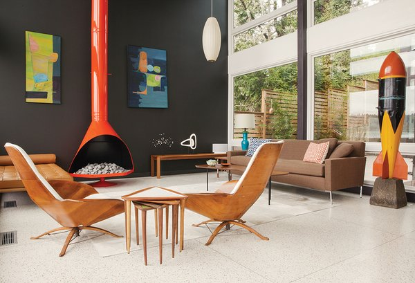 "In the living room of a remodel in Seattle, the fireplace was powder-coated orange to complement the vintage furnishings. The sofa is from Design Within Reach; the coffee table is by Alexander Girard for Knoll. A pair of undated paintings by Arthur L. Kaye hang on a wall painted in a Benjamin Moore hue custom matched to the outside of the window frames. The triangular nesting tables are a vintage find. ""They're always billed as 'guitar pick tables,'"" resident Sally Julien says."