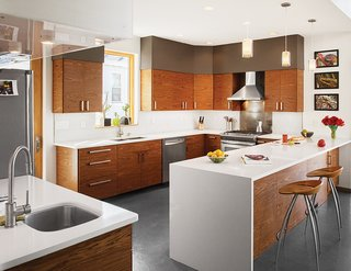 "In the kitchen, Echo pendants from Tech Lighting hang above quartz countertops from Cambria. ""The cabinets were a cost-driven solution,"" Moss says. ""The kitchen was developed around Ikea cabinet boxes, but we sourced the semi-custom cabinet front panels through an online retailer, 27estore.com."" The range is by Frigidaire and the wall-mounted range hood is by Cavaliere. A pair of Lyra stools by Design Group Italia for Magis round out the space."