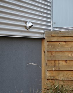 """The use of corrugated metal ""was a very cost-effective cladding solution that pays homage to the metal-clad warehouse buildings in Lawrenceville,"" Moss says, ""but it does so in a manner that matches the scale of most of the lap-siding homes in the area."" The windows are mostly standard sizes from Pella."