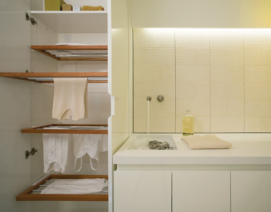The cabinetry cleverly conceals everything, including a custom drying rack.  Photo 4 of 5 in Bright Modern Laundry Room We'd Actually Like to Spend Time In