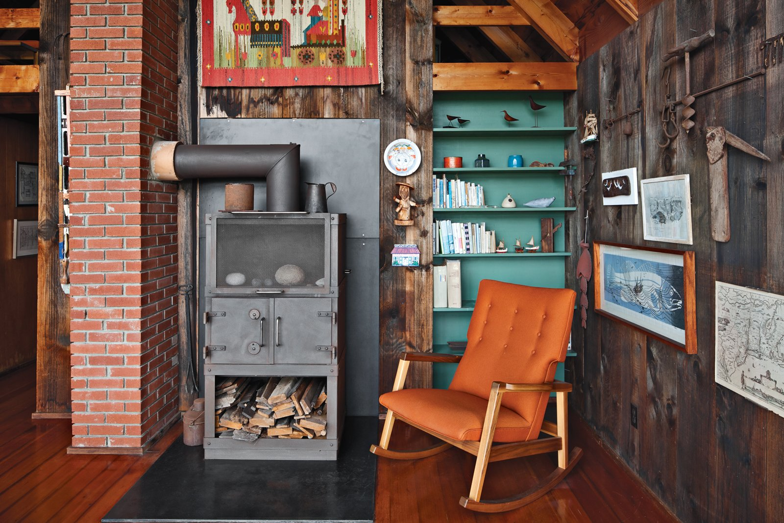 Living Room, Medium Hardwood Floor, Chair, Wood Burning Fireplace, and Shelves Inside the house, a relatively new Rais wood-burning stove is next to a Risom Rocker from Design Within Reach, a 2009 piece from the designer.  Photo 3 of 13 in Jens Risom's Block Island Family Retreat