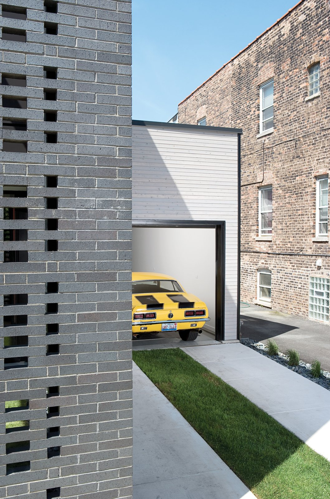 Garage and Attached Garage Room Type When open, the garage enables the owners to work on their vehicles while visiting with neighbors who do the same.  Photo 10 of 10 in The Brick Weave House in Chicago