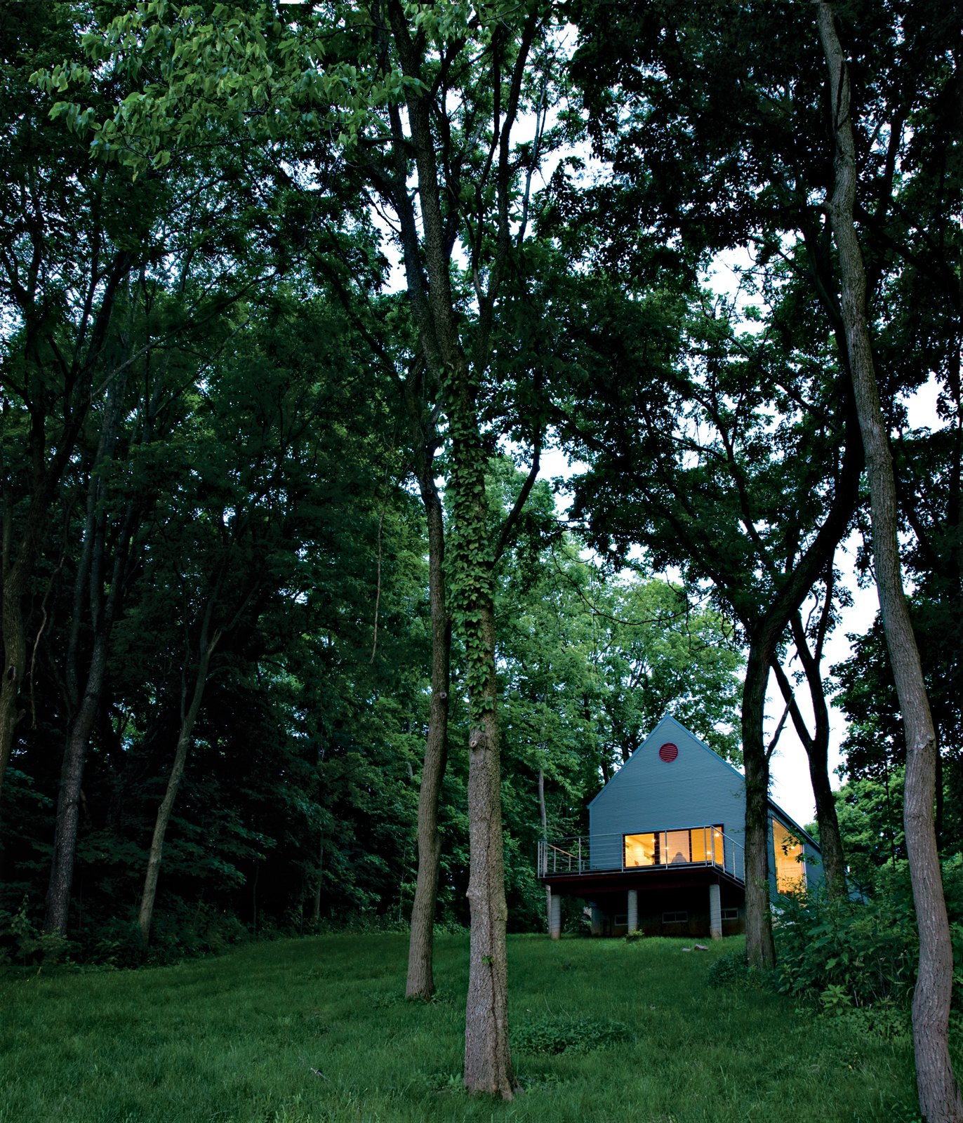 Grass, Trees, Slope, Back Yard, Exterior, and House Building Type Lauren Ewing's stylish but unassuming shotgun-style house in Vincennes, Indiana, is set into a hill overlooking a field she has known since childhood.  Photo 14 of 20 in 20 Modern Homes From the Midwest from Bringing It All Back Home