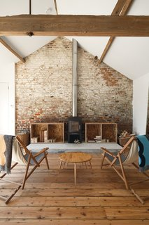Subverting the traditional, conservatively cozy British barn conversion, Carl Turner created a getaway in rural Norfolk for himself and his friends to visit, repose, and consider the beauty of agrarian minimalism. In the converted barn, a modern fireplace with a sleek, shiny chimney contrasts with the wide, reclaimed wood floorboards and textured exposed brick wall.