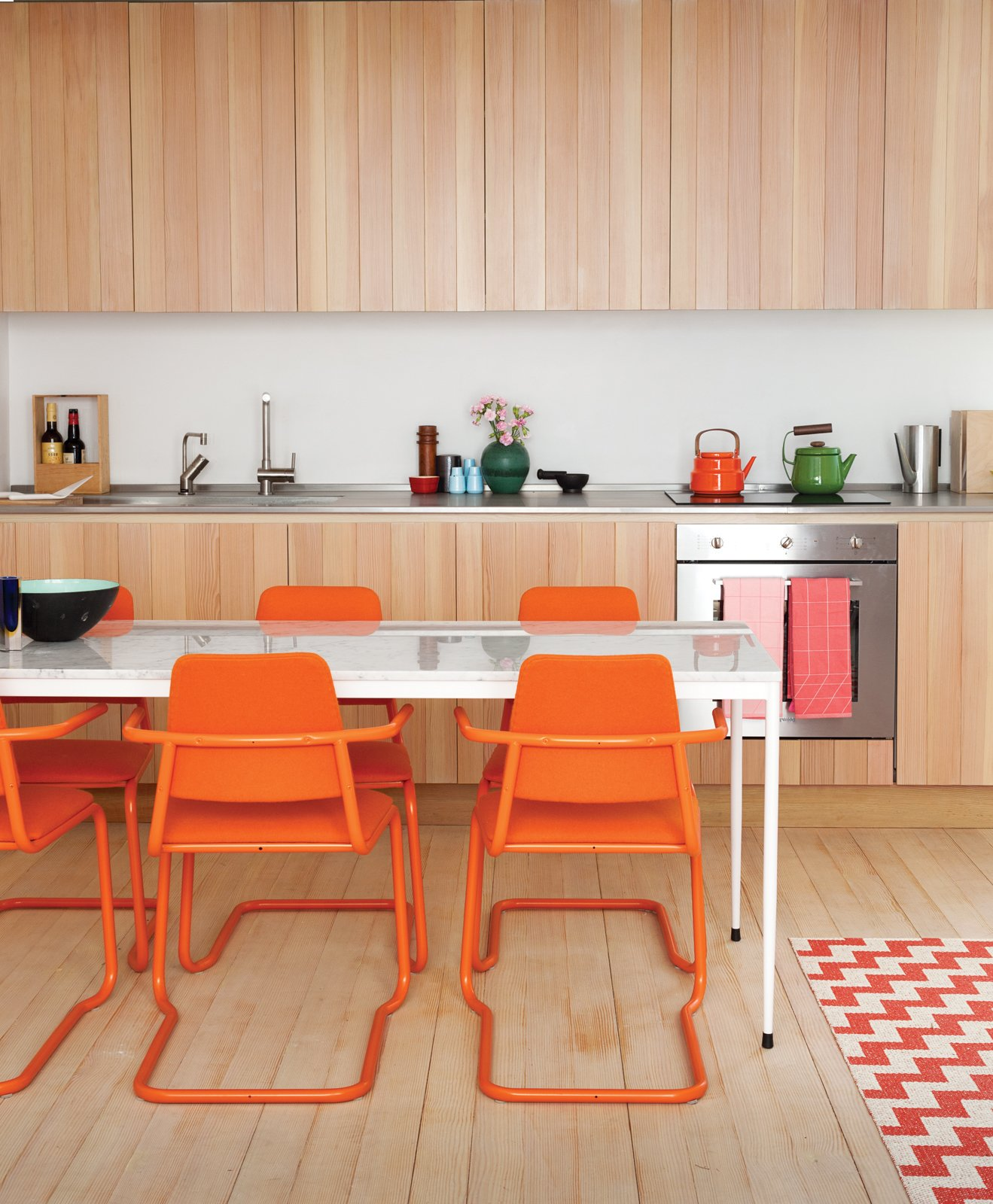 In this custom-built London guesthouse kitchen designed by Studiomama, lustrous vertically clad cabinetry achieves additional depth with the addition of the chairs, which were picked up for $15 each at a local market and powder coated in bright orange. Tagged: Kitchen, Metal Counter, Wood Cabinet, Light Hardwood Floor, Wall Oven, and Cooktops.  Photo 1 of 7 in How-To Design with Patterned Rugs from A Colorful, Custom-Built Guesthouse in London