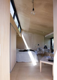 The interior is small, but comfortable. It fits a double bed, coffee table, and chair. The bed is recessed into the wall so as not to waste any space. Natural light floods the interior from a clerestory.