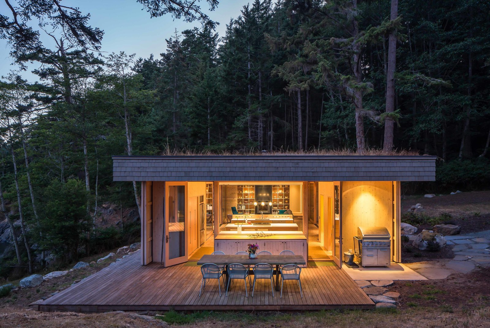 """Wood Patio, Porch, Deck, Large Patio, Porch, Deck, Exterior, Back Yard, House Building Type, Green Roof Material, Wood Siding Material, Cabin Building Type, and Flat RoofLine One of the main goals of the construction was to do as little harm as possible to the existing environment, which includes waterways that salmon depend upon. Herrin and his team created a garden roof that covers the full extent of the home to meet this objective. """"This helps control storm water runoff and also replaces lost insect habitat—insects being a critical food source for juvenile salmon,"""" he says.  Photo 99 of 101 in 101 Best Modern Cabins from San Juan Islands Residence"""
