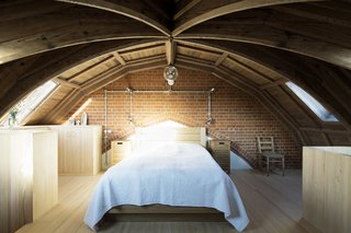 The bedroom is located on a mezzanine just below the roof of the church. The minimal decor and simple arrangement of the room reflect the client's modest tastes. The small pewter spotlights and pendant by Holloways of London connect to an exposed galvanized conduit that is set against the brick above the bed.
