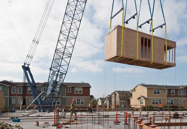 A construction team assembles the individual units.