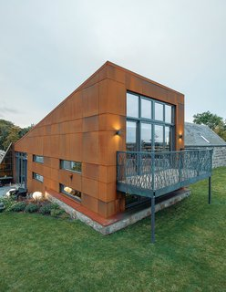 A balcony of steel panels with unusual cutouts creates a unique balcony on this weathered-steel home.