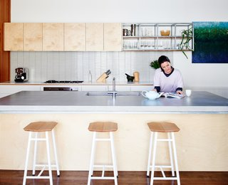 In the kitchen, Dedo stools by Simone Simonelli for Miniforms pull underneath a poured-in-place concrete countertop.