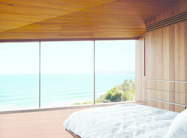 The couple, both surfers and beach lovers, wake up to stunning views of the azure-blue Southern Ocean in their otherwise monochromatic eucalyptus master bedroom. Wardle's firm designed the bed base, and the panel in the ceiling hides a television.  Photo 7 of 9 in A Eucalyptus-Lined Oceanfront Home in Australia