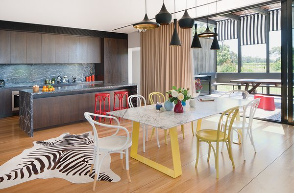 """Tom Dixon pendant lamps hang above a steel-and-marble dining table by Chris Connell topped by Kate Hume vases and surrounded by painted Thonet chairs. The wood-veneer cabinetry in the adjacent kitchen complements the rich Grigio Carnico marble on the island and backsplash. """"The kitchen has a deliberately dark palette,"""" James says.  Photo 2 of 8 in Living Simply on a Lush Australian Estate"""