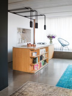 By using color, wood, and polished concrete floors, this apartment in Berlin is full of personality. In the kitchen, polished statuario marble covers both the island's countertop and the backsplash in the custom kitchen cabinet block. PSLAB designed the light fixtures, and the island has open shelving incorporated into it for easy access to cookbooks and other reading material.