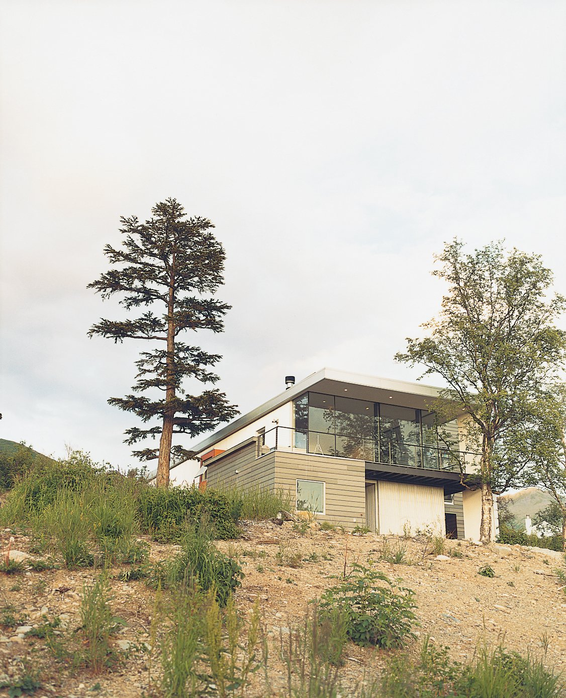 Exterior, Stucco Siding Material, House Building Type, and Wood Siding Material Though the Cook Inlet is nearby, from the street, the house's simple facade gives little indication of the sights that await a visitor.  Photo 4 of 9 in Alaska: The Final (Architectural) Frontier