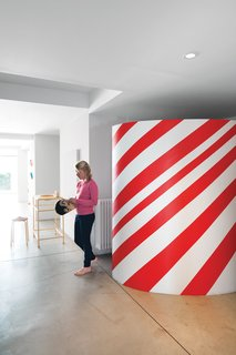 Daughter Oona stands near the candy-striped wardrobe in the entryway.