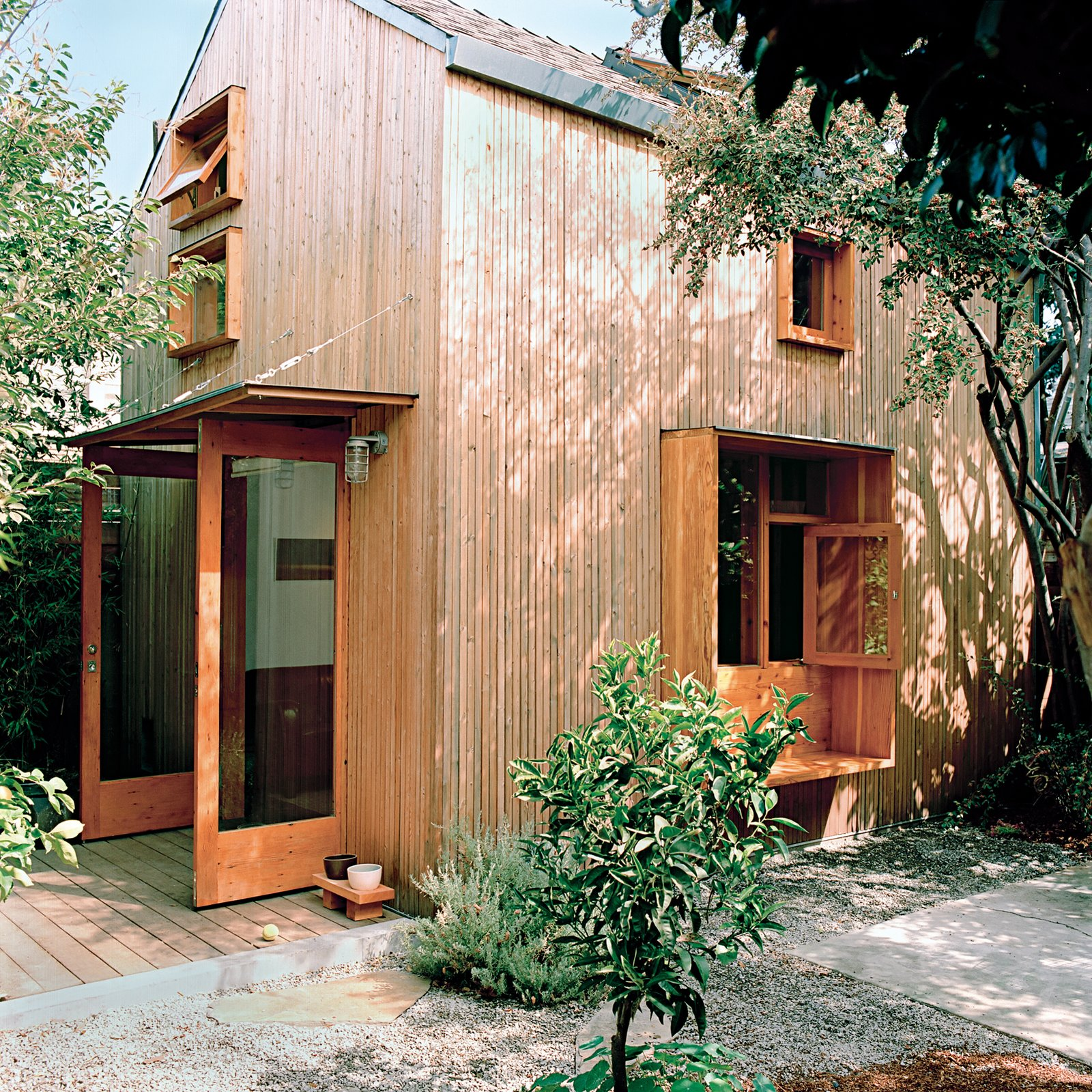 "Exterior, House Building Type, Shingles Roof Material, and Wood Siding Material Outside, the couple clad the house with a rain screen of 1.5-by-1.5-inch strips of spruce to create a ""modern rustic barn."" The extra-deep sills of the first-floor window become a bench on the outside and a shelf on the inside.  Photo 3 of 9 in Built-In Style"