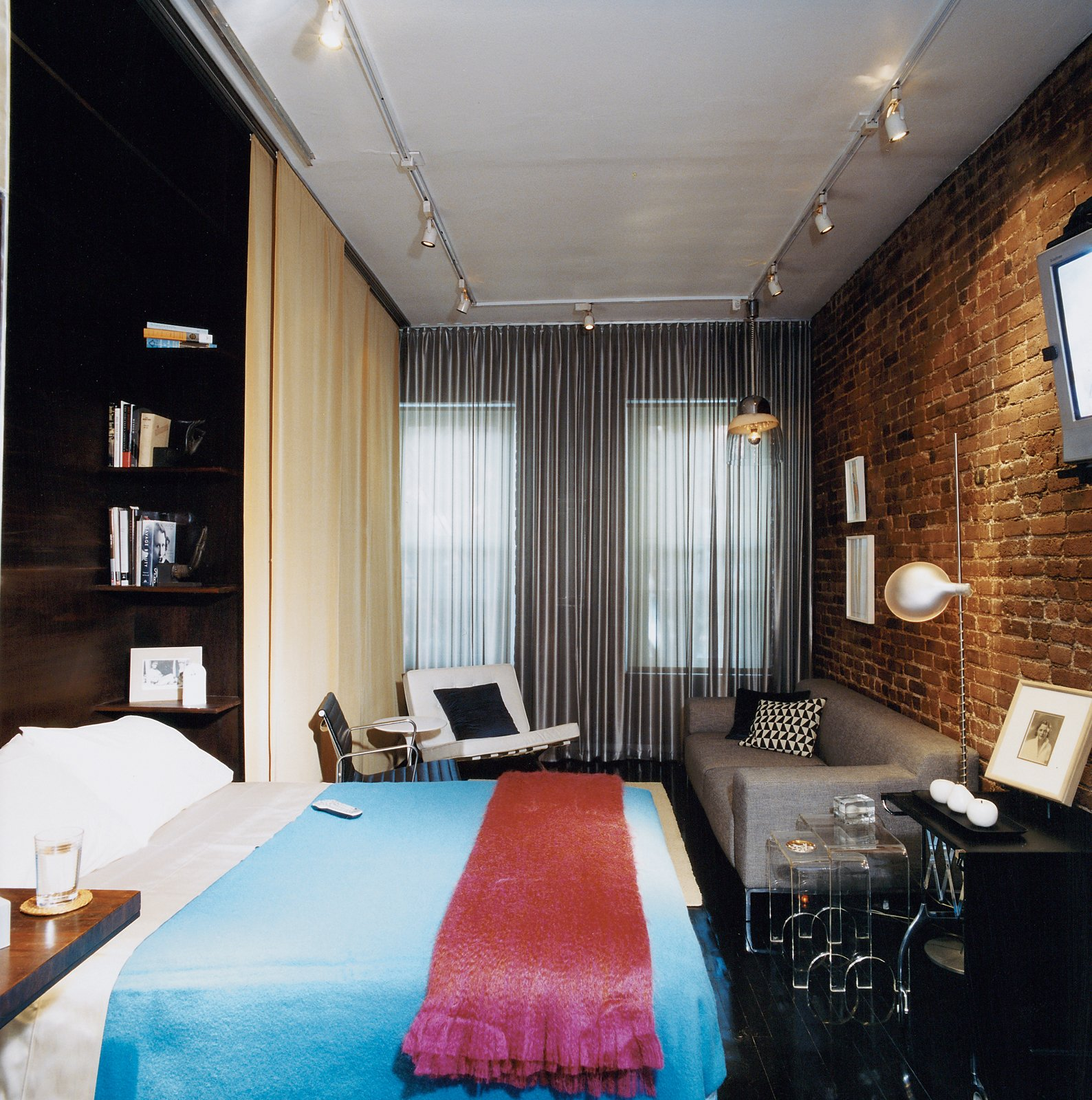 """Bedroom, Bed, Shelves, Track Lighting, Dark Hardwood Floor, Pendant Lighting, Night Stands, and Chair """"I think of the bed as intimate space,"""" Hughston says, """"and putting the bed away—having it out of sight when not in use—is satisfying."""" The custom-designed Murphy bed, concealed by day behind the gold curtain is well built; it's ergonomically easy to lower and has a firm sleeping surface.  Photo 4 of 6 in A 400-sq-ft New York Apartment Gets a Second Chance"""