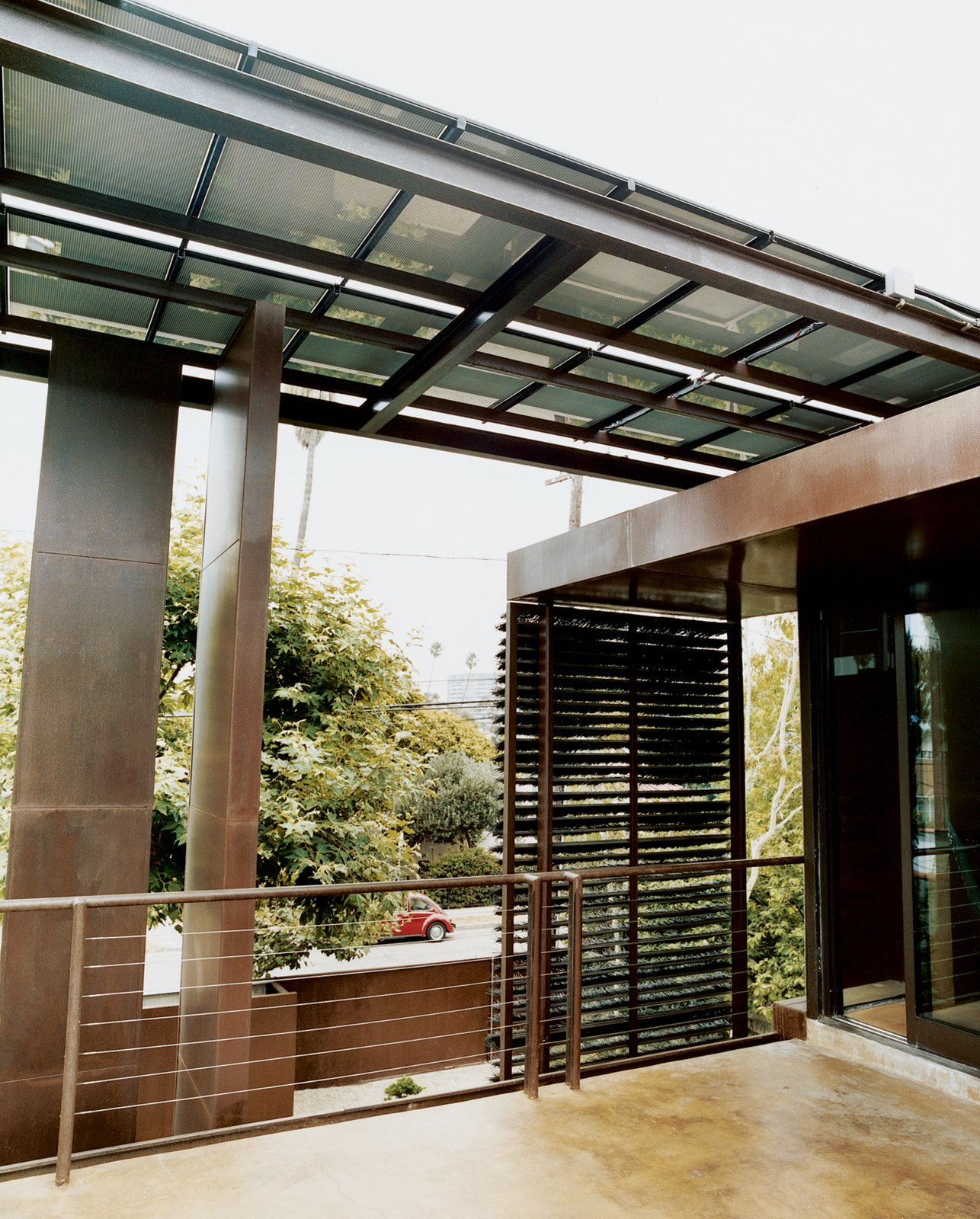 Outdoor and Small Patio, Porch, Deck A steel-beam canopy with solar panels shades the house and provides electricity.  Photo 4 of 8 in Solar Inspiration