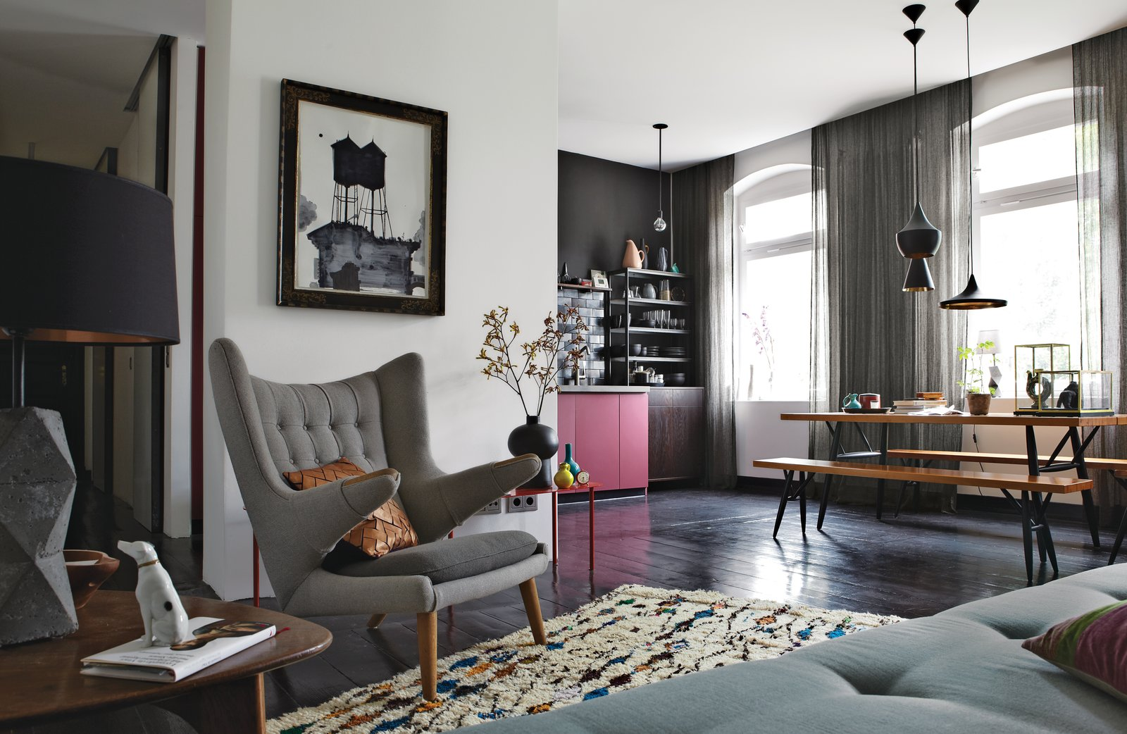 The old wood floors throughout the open-plan space are painted a dark eggplant. The vintage PP19 armchair is by Hans J. Wegner for PP Møbler. The painting above it is by Ruben Toledo, a friend of Peter Fehrentz, the resident. A trio of Tom Dixon lights hangs over the Pirkka dining table, with bench seating by Ilmari Tapiovaara for Artek. The Berber rug is from Morocco, purchased from the Paris shop Caravane.