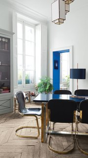 10 Dreamy Parisian Homes - Photo 1 of 10 - The dining room features 1970s leather-and-brass dining chairs and a table concocted from a brass-and-silver base and a custom lacquered top. The cheerful blue paint enlivening the doorway is from Emery & Cie.