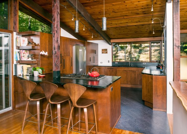 Embracing the natural environs of their family home—a 1970 Deck House nestled among 175-foot-tall tulip poplar trees—residents Darren Selement and Cathryn Rich updated the kitchen with a rich material palette of wood and stone. Cherner barstools are paired with custom, cherry-stained alder cabinets by Holiday Kitchens, Barocca soapstone countertops, and flooring from Globus Cork.