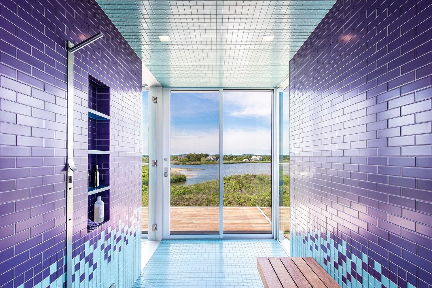 Bath Room, Ceramic Tile Wall, Ceramic Tile Floor, Ceiling Lighting, and Open Shower Consider this lively bathroom that sits within a recently completed waterfront home in Bridgehampton, New York. Situated on two-and-a-half acres of land with 360-degree views of the nearby bay and ocean, it's covered with brightly colored floor-to-ceiling tiles that reflect the shades of the neighboring water. One step through the sliding glass doors and you'll find yourself on an open terrace.  Photo 15 of 20 in 20 Bathrooms With Transformative Tiles from One of These Ultra-Modern Bathrooms Could Be the Escape of Your Dreams