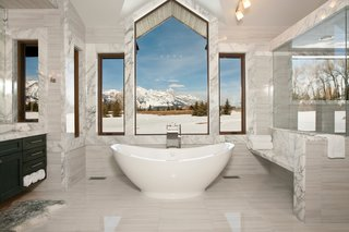 Making our way to Jackson Hole, Wyoming, this master suite bathroom is nestled within a mountain retreat that sits on five acres of private land. Slabs of Carrera marble line the space while the central window overlooks the Grand Teton national park. Placed at the edge of the bathroom is a 50-square-foot shower with steam capabilities.