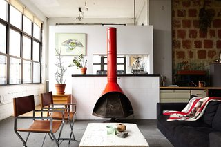 """""""I'm not trying to hide anything. I wanted to stay true to the industrial look,"""" explains Owen Wright, the owner of this Brooklyn loft. Owen works with his building's landlord and consequently has accrued countless pieces of furniture from both former tenants and Craigslist—including this 1960's bright orange metal fireplace and pair of steel frame chairs Owen had reupholstered. A BoConcept sofa and coffee table Owen constructed himself complete the living room."""