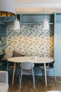 Graphic wallpaper complements the color scheme and adds visual interest. Adding bench seating and built-in shelves around the La Redoute table helps to delineate this space as a study and dining area within the larger room.
