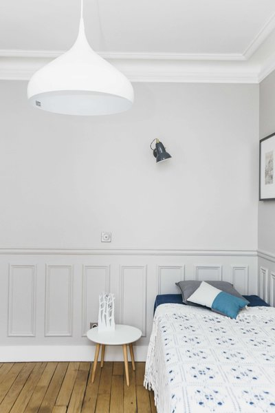 The charm of original wood floors, wall paneling, and thick crown molding is brought into the 21st century with a coat of crisp white paint and soft gray walls. Minimalist furnishings and fixtures, like an undulating white pendant and a small white bedside table, keep it feeling modern.