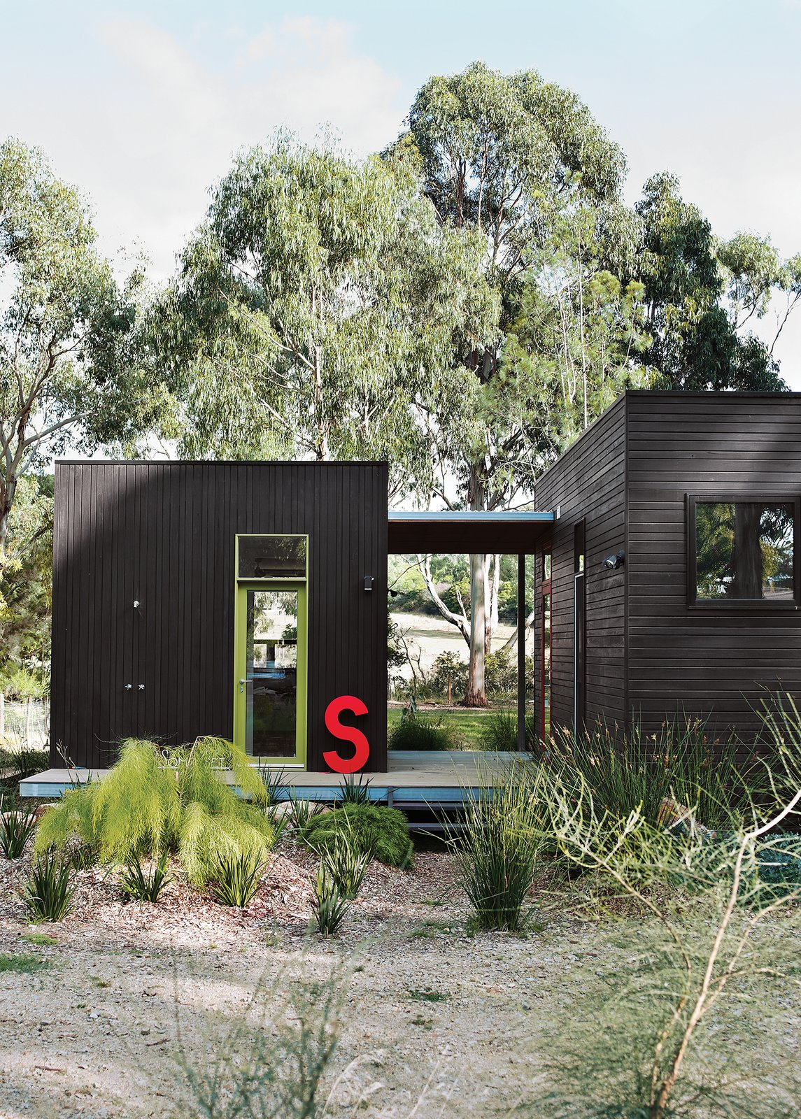 For her family's house near Melbourne, Anna Horne created a series of prefab wood modules using a design from the company Prebuilt. She found the old industrial letter at a factory; it stands for Somerset, the name of the house.  Photo 6 of 11 in The Best Prefab Homes in Australia from Dark and Modern Black Houses
