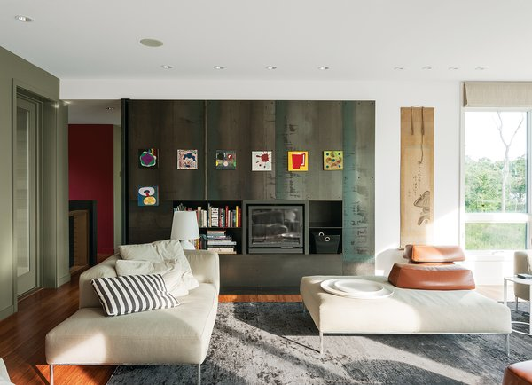 The fireplace wall, a Resolution: 4 signature, is made of 14-gauge hot-rolled steel panels with storage components in one-eighth welded steel. On one side is a pivoting privacy panel that allows the guest wing to be closed off. Art attaches to the metal with magnets.