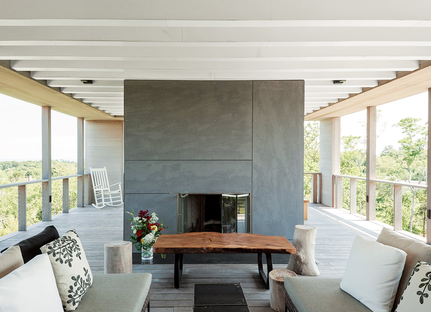 Outdoor, Large Patio, Porch, Deck, and Wood Patio, Porch, Deck On the rooftop deck is an outdoor fireplace clad in cement board panels, plus a custom wych elm table by Arnold d'Epagnier and Charles Outdoor sofas by B&B Italia.  Photo 10 of 11 in An Unconventional Prefab on Fishers Island