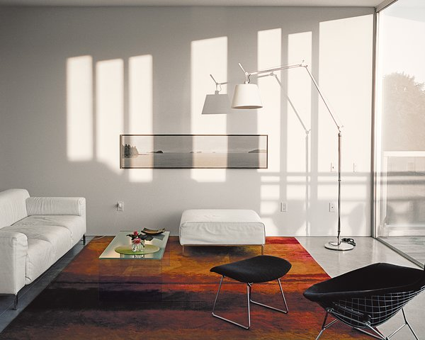 The living room is furnished with a Bird chair and ottoman by Harry Bertoia, a Greg sofa by Zanotta, a CK 10 rug by Calvin Klein, and a Tolomeo lamp from Artemide.  Photo 3 of 7 in A Modern Multiunit Prefab Prototype in Vancouver