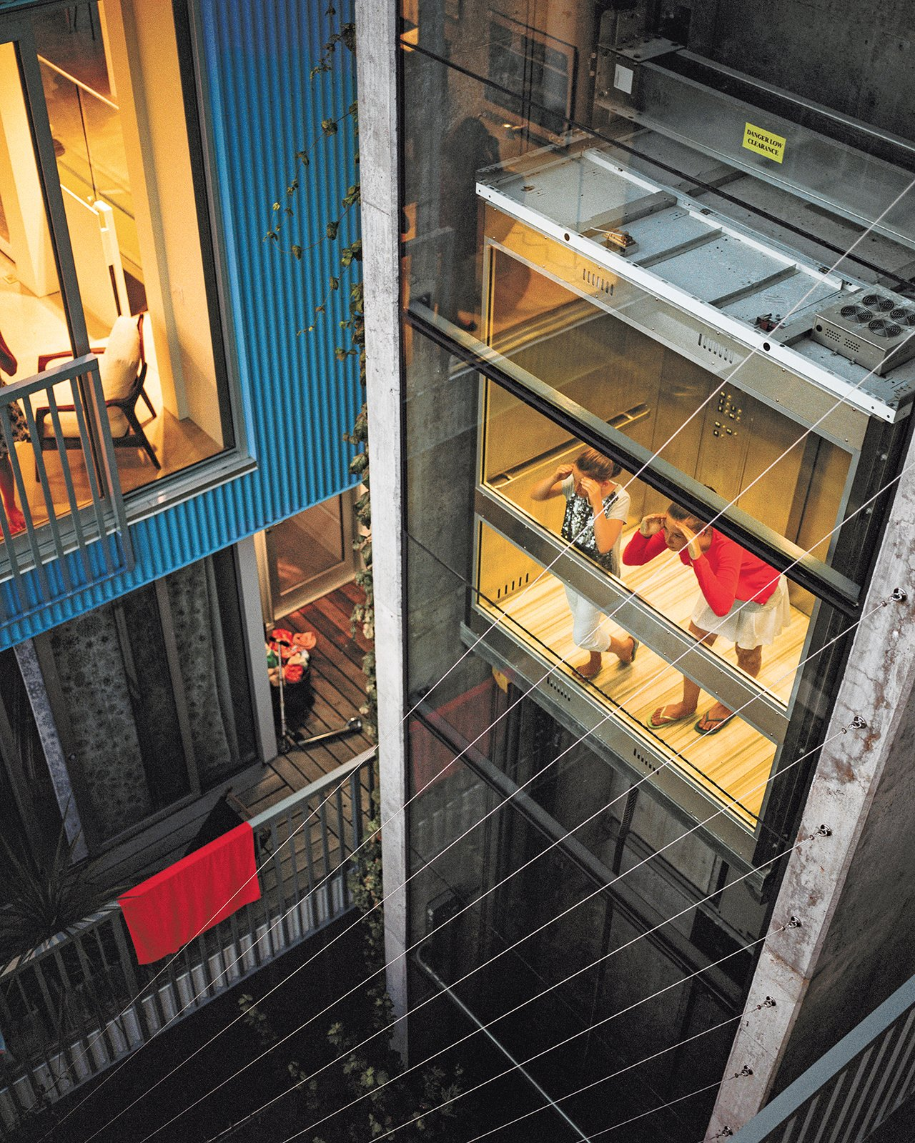 "The couple's daughters, Fiona and Olivia, try out the central elevator, which is shared by all the owners and tenants and was designed, says Lang, ""to encourage neighbor interaction.""  Photo 4 of 7 in A Modern Multiunit Prefab Prototype in Vancouver"