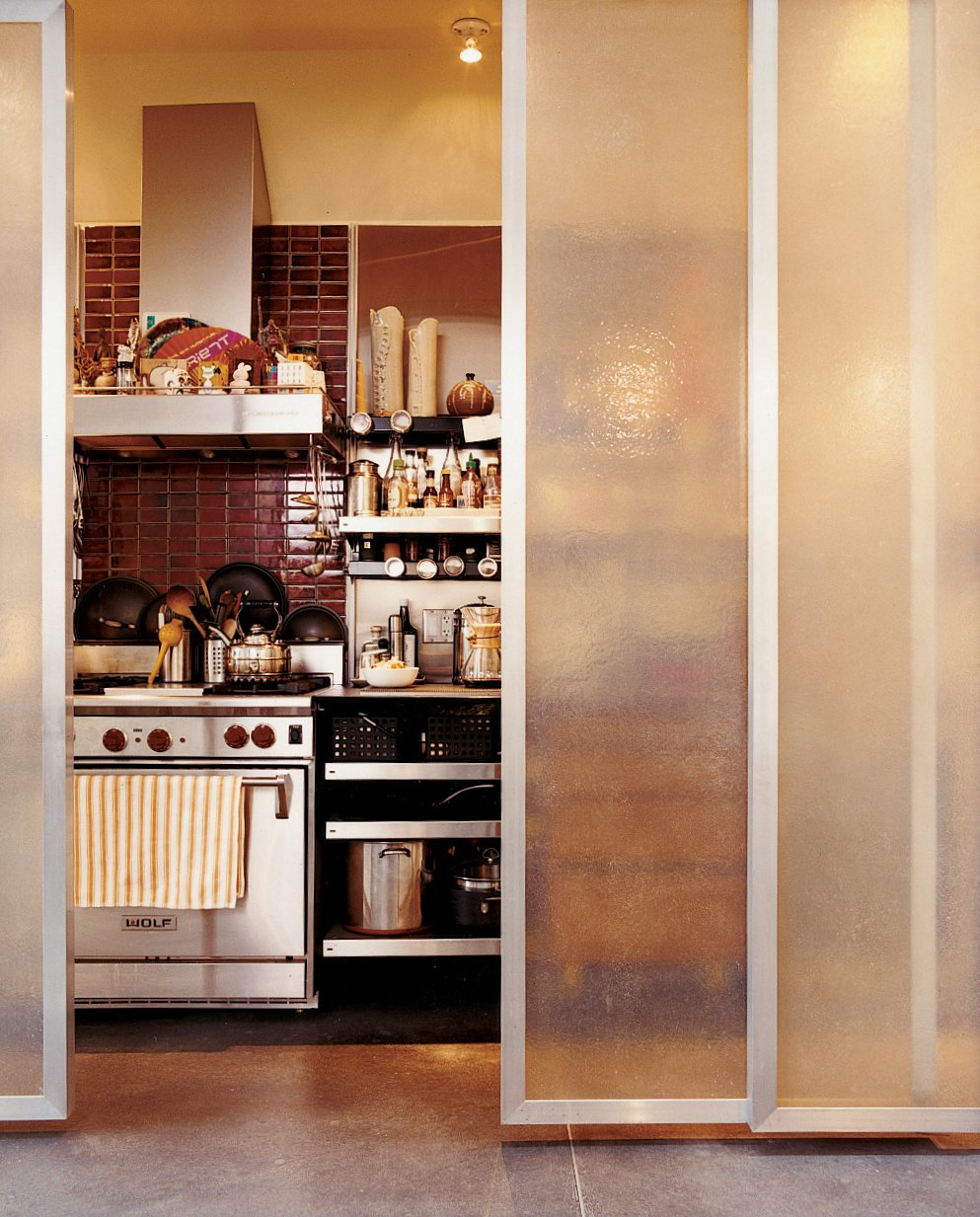The kitchen and Baker's home office, which has artwork and inspiration pinned above the desk, are aligned behind sliding fiberglass-and-bamboo shoji screens. Devoid of cabinetry, the kitchen is fitted out with industrial cantilevered shelving from E-Z Shelving Systems in Kansas City. The red tiles behind the stove are from Heath Ceramics.  Photo 5 of 9 in Mission Statement