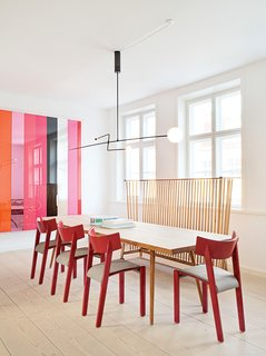 In the dining area of the kitchen, a Mobile Chandelier 3 by Michael Anastassiades is suspended above a table from local cabinetmaker Københavns Møbelsnedkeri. Vintage red dining chairs by Ralf Lindberg mingle with an Ilse Crawford bench for De La Espada. Photos courtesy the Apartment.