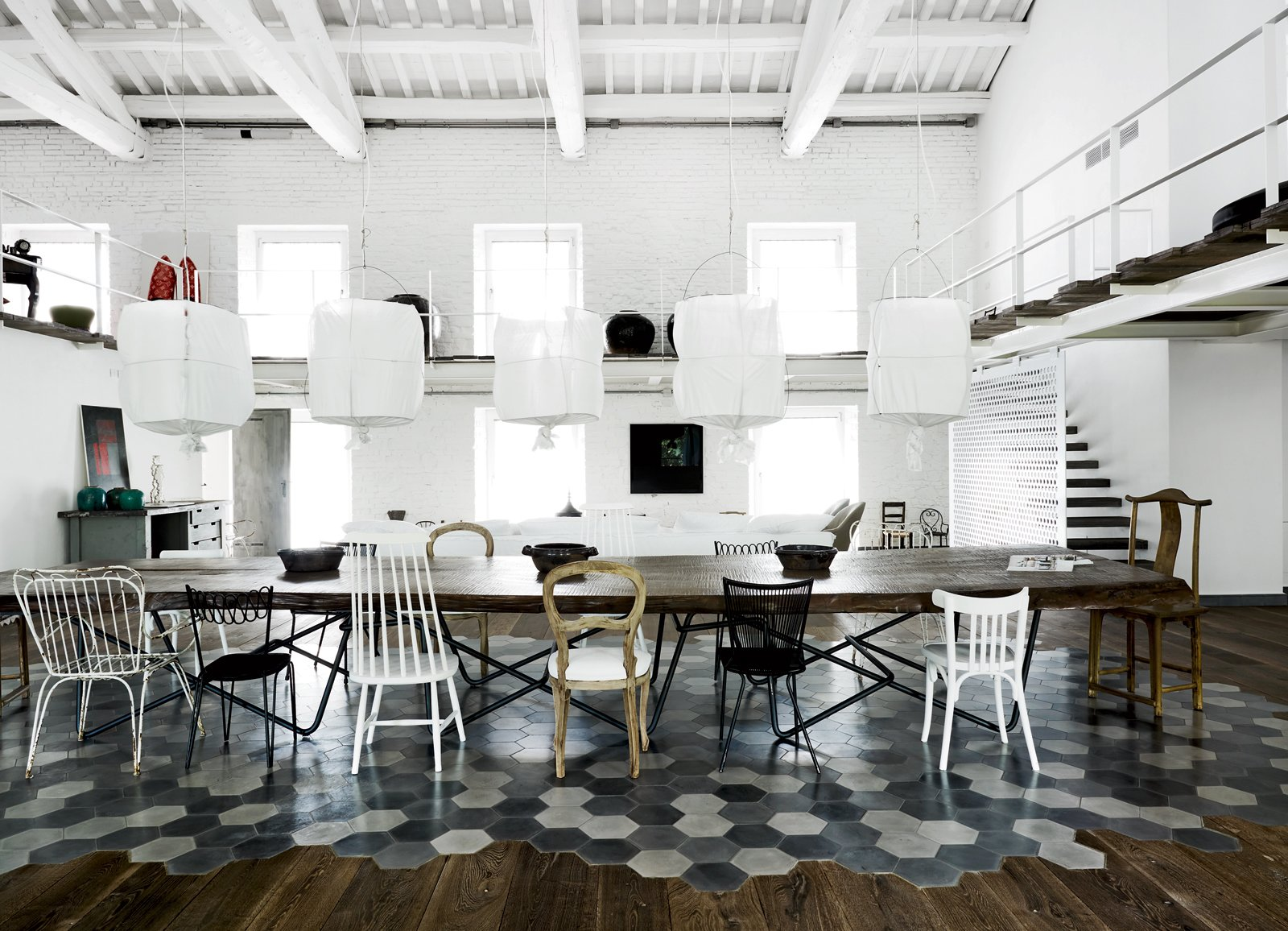 Dining Room, Table, Chair, Pendant Lighting, Dark Hardwood Floor, and Ceramic Tile Floor Visitors pass by a sentry wall of lamps from Design House Stockholm on their way to the airy living-dining room with its 52 windows.  Photo 1 of 11 in Paola Navone's Industrial Style Renovation in Italy