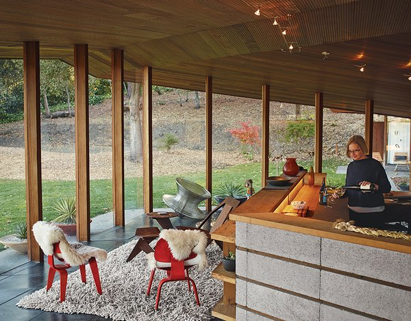 Lambert pours wine in the kitchen, which is defined by a low concrete-block wall and serves as the home's central core. The seating-area chairs are from Herman Miller.