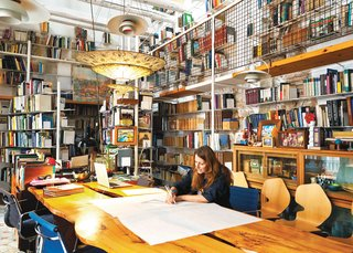 In her library, Tagliabue works at a table designed by Miralles.
