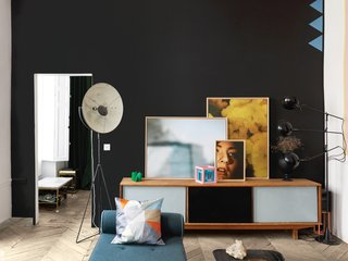 A vintage 1950s credenza discovered in Paris supports three works by Aumas and two Sol LeWitt–inspired cubes used in one of his window displays. The daybed is an eBay purchase reupholstered in fabric from Kvadrat and the dark paint is from Dulux Valentine. Aumas found the photographer's lamp at a Brussels flea market.