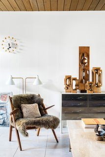 Mark Neely and Paul Kefalides's living room is decked out with the couple's vintage finds, including a Hans Wegner Sawback chair (the fur throw obscures an area needing repair), a George Nelson Ball Clock, a DF-2000 cabinet by Raymond Loewy, a light designed by Greta Von Nessen, and a suite of Brian Willsher wooden sculptures, one of Neely's many collections.