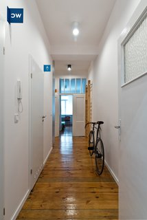 The subdued white and grey interiors help highlight details such as the flat's original wood floors. Apart from the blue bathroom identifiers and room markers, the only other colors used are the occassional orange and green, the same hues that are used in several of Wierciński's other projects.