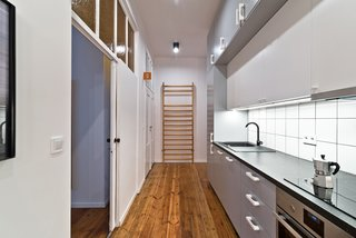 """Working within the constraints of a modest budget, the design team creatively mixed custom-designed pieces with more affordable items. For example, the shared kitchen features a Franke kitchen sink and IKEA cabinetry and appliances. Framing the kitchen wall, an old gymnasium ladder adds an historical touch. The biggest challenge of the project, says Wierciński, was to """"execute a low budget project with a unique original style."""""""