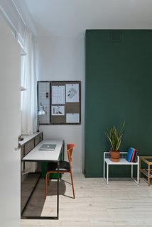 One student bedroom features the second green accent wall. Each bedroom is about 140 square feet and includes places for sleeping and studying, plus built-in IKEA wardrobes. The custom desk is paired with an orange IKEA chair. The small metal accent table and magnetic wall board are also by Wierciński.